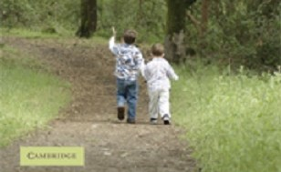 Image is of a book cover. Image is zoomed in to only the picture on the book cover, which is picture of a path going through a field with trees. There are two little boys on the path holding hands.