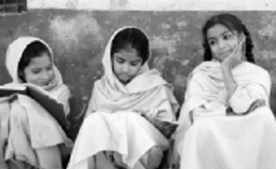 Image is of three young girls sitting in front of a wall.