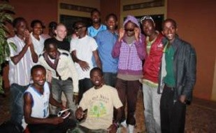 Image is of Mike Brand and his family at the Agahozo Shalom Youth Village. Image is of thirteen youths.