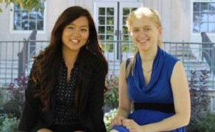 Image is of two women, Sharon Hwang (left) and Molly Rockett (right). They are pictured sitting, in front of a fence and a building