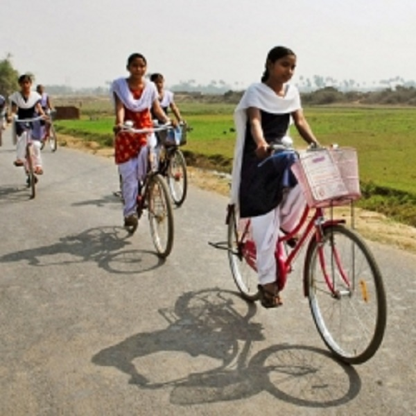 Image is of four young girls from India on bicycles