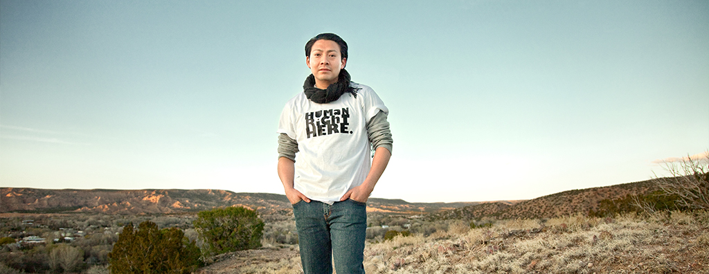 "Image is from the Human Right Here Campaign. Image is of a person standing outside. They are wearing a shirt with the text, ""Human Right Here"" on the shirt"