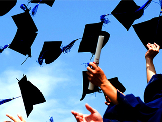Image of graduation caps thrown in the air. A few student hands holding diplomas are visible as well