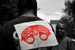 "Image is related to a student internship; image is of two people, one in the back-round and one in the foreground. The person in the foreground has their back to the camera, with a sign on their back. The sign says ""occupy justice."" Below the words on the sign there are handcuffs."