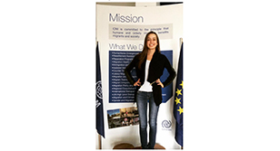 "Image is a picture of Dhurata Lluhani in front of a poster that says ""Mission"" and ""What We Do"""