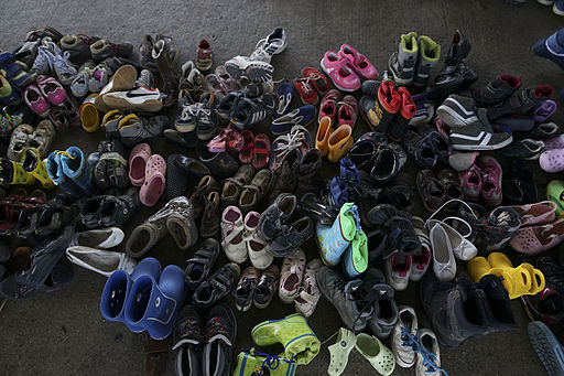 Image is of several dozen pairs of children's shoes captured during a refugee crisis