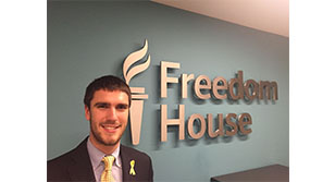 Image of Andrew posing in front of a wall with the freedom house logo on it.