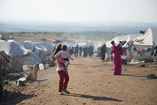 Syrian refugees walk outside their tents at a camp for internally displaced persons in Atmeh, Syria, adjacent to the Turkish border.