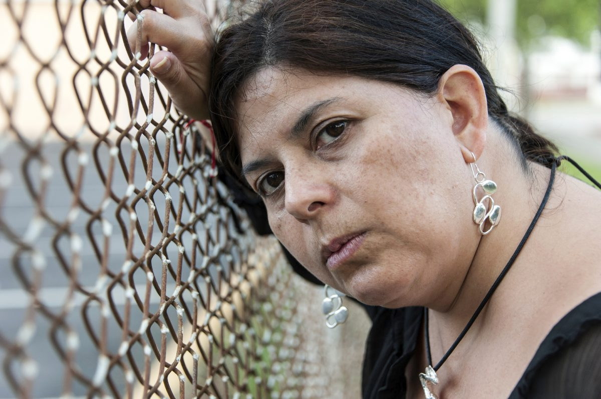 Image is a woman's face. She is leaning against a rusted fence.