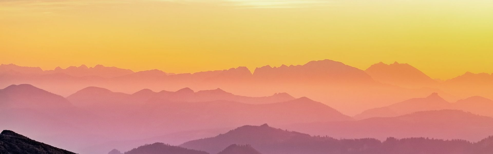 rainbow colored sunset over misty mountains